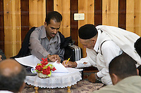"""Tripoli, Libya.  Muslim Wedding Celebrations.  Groom's Uncle Signing Marriage Contract, while Sheikh (""""Ma'doun"""") Officiates."""