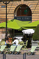 A wine bar with seating outside with green parasols shading from the sun and two people sitting by a table drinking, Reims, Champagne, Marne, Ardennes, France
