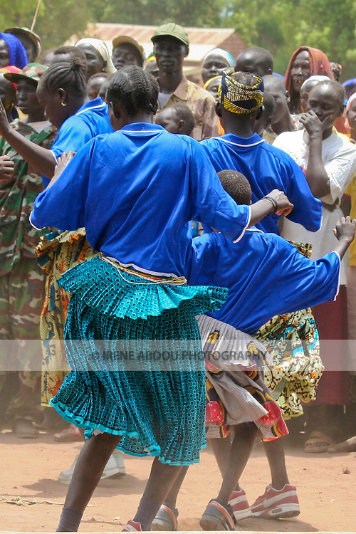 A group of Kakua women passionately shake their bodies across Freedom Square's dirt dance floor. Traditional performances like this one grace the intermissions of public events, such as government rallies and social development events.  Here, the international public health organization, Population Services International (PSI), in partnership with the South Sudan Ministry of Health, raises awareness about malaria on Africa Malaria Day.