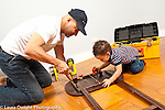 Toddler boy age 18 months at home with father modeling imitation interested in how he uses drill and using small drill