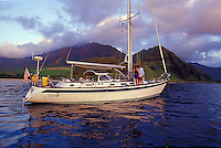 Couple on deck of their 48 foot sailboat off Makua Beach, West Oahu, Hawaii
