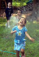Children cooling off by spraying water in the back yard.  Model released