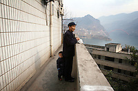 CHINA. Chongqing Province.  A man and child in the town of Wushan, which lies on the banks of the Yangtze and at the entrance to the 3 Gorges. The flooding of the three Gorges, by damming the Yangtze near the town of YiChang, has remained a controversial subject due to the negative environmental consequences and the displacement of millions of people in the flood plain. The Yangtze River however is reported to be at its lowest level in 150 years as a result of a country-wide drought. It is China's longest river and the third longest in the world. Originating in Tibet, the river flows for 3,964 miles (6,380km) through central China into the East China Sea at Shanghai.  2008.