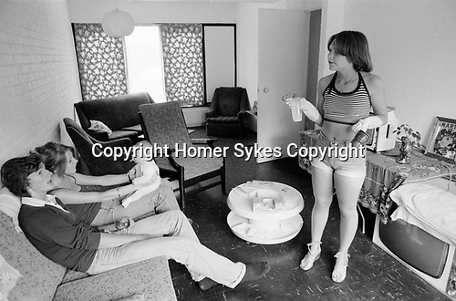 1970s UK, middle class young adults just moved into modern home on a recently built new housing development. Young mum in fashionable Hot Pants her new baby is being played with by a couple of friends from London who have come up for the day to see the new house and baby.  1977 England. Through living room dining room, TV on the floor too much furniture nothing yet properly organised. Milton Keynes Buckinghamshire