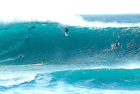 Surfers on the the treacherous winter wave known as the Banzai Pipeline at Ehukai Beach on the north shore of the island of Oahu