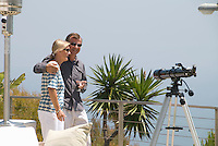 Man and Woman on garden terrace overlooking Palm tree and Pacific Ocean.  Telescope and heater visible in shot.