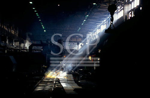 Sofia, Bulgaria. Man cutting steel sheets with sparks flying in Dickensian steelworks with shafts of sunlight from high windows.