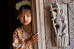 Standing at the door of a Burmese temple a young girl wears traditional face cosmetic called thanaka painted in the shape of a leaf. Thanaka is a paste made from the bark of the thanaka tree and it is popularly used in Myanmar.
