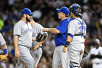 Toronto Blue Jays pitcher Todd Redmond (58) gets the ball from manager John Gibbons (5) during a pitching change as Dioner Navarro (30) looks on during a game against the Chicago White Sox on August 15, 2014 at U.S. Cellular Field in Chicago, Illinois.  Chicago defeated Toronto 11-5.  (Mike Janes/Four Seam Images)