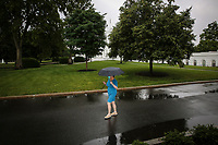 A woman walks in front of the White House in a light rain on June 11, 2020 in Washington, DC.<br /> Credit: Oliver Contreras / Pool via CNP/AdMedia