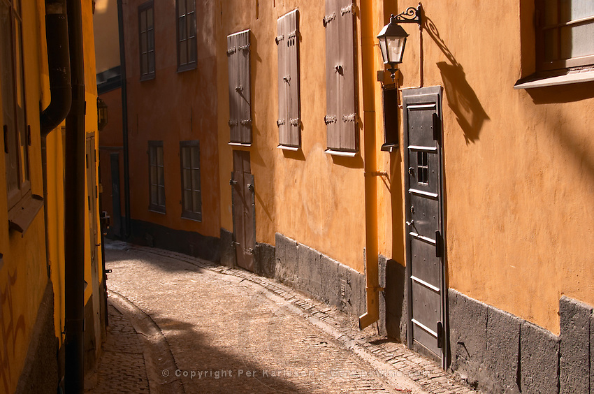 A cobblestone street in Gamla Stan the Old Town in Stockholm. an iron cellar door and an old lamp casting a long shadow on the terracotta wall the street curving to darkness windows with closed shutters Stockholm, Sweden, Sverige, Europe