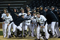 The Wake Forest Demon Deacons gather at home plate awaiting the arrival of William Simoneit (not pictured) after he hit a walk-off home run in the bottom of the ninth inning against the Louisville Cardinals at David F. Couch Ballpark on March 7, 2020 in  Winston-Salem, North Carolina. The Demon Deacons defeated the Cardinals 3-2. (Brian Westerholt/Four Seam Images)