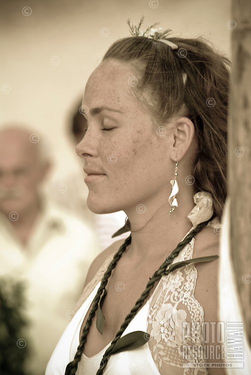 Lovely young local bride reflecting on the future with her husband at her wedding at Ke'iki Beach, North Shore