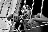 A young Cuban man stands behind the door grill during a hot summer afternoon, Santiago de Cuba, Cuba, 31 July 2008.