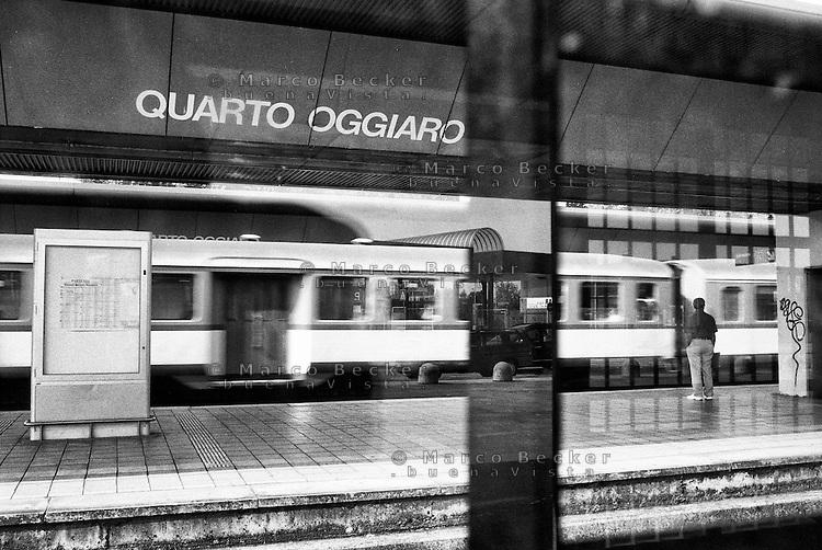 Milano, quartiere Quarto Oggiaro, periferia nord. Una persona in attesa sulla banchina della stazione ferroviaria osserva il passaggio di un treno --- Milan, Quarto Oggiaro district, north periphery. A man waiting on the platform at the railway station and watching a train passing by