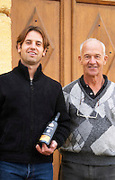 Philippe Viret owner and winemaker holding a bottle of cuvee Emergence and his father Alain. In front of the winery.   Domaine Viret, Saint Maurice sur Eygues, Drôme Drome France, Europe