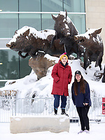 Jordan Smith (left), a junior at the University of Arkansas, and Cora Butcher-Spellman, a recent graduate student graduate, explore the snow and ice accumulation on the Wild Band of Razorbacks monument on the northeast corner of Donald W. Reynolds Razorback Stadium on the campus of the University of Arkansas in Fayetteville. The National Weather Service forecasts partly sunny skies with a high near 28 degrees today. Check out nwaonline.com/210218Daily/ and nwadg.com/photos for a photo gallery.<br /> (NWA Democrat-Gazette/David Gottschalk)