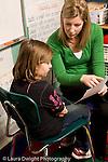 Education Elementary school Grade 2 female teacher discussing work with female student praising her vertical