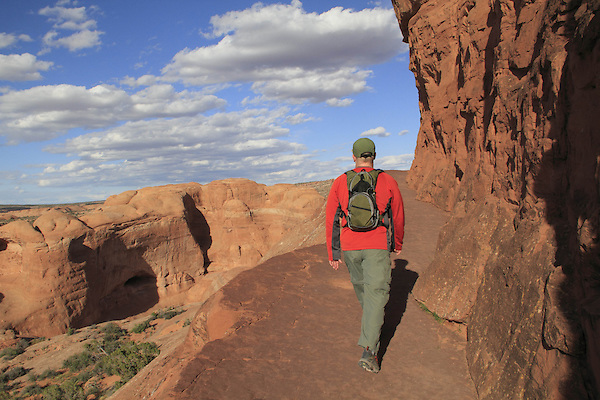 Man on hiking trail leading to Delicate Arch in Arches National Park, Moab, Utah, USA. .  John offers private photo tours in Arches National Park and throughout Utah and Colorado. Year-round.