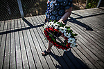 A woman holds a wreath in memory of Elizabeth Saw during a memorial ceremony over the Yarkon river in Tel Aviv Tuesday July 4 2017. Saw was one of the victims when four members of the Australian delegation to the 15th Maccbiah games died in a tragic  catastrophic failure of a pedestrian bridge over the Yarkon River during the opening ceremony of the Games. Photo by Eyal Warshavsky