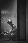 Scan of vintage print. File#76-252H #10. Geisinger Medical Center, Danville, PA. Nurse at night making entries in hallway. 1976