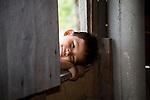 Belizean boy in the window of his home near Punta Gorda, Belize