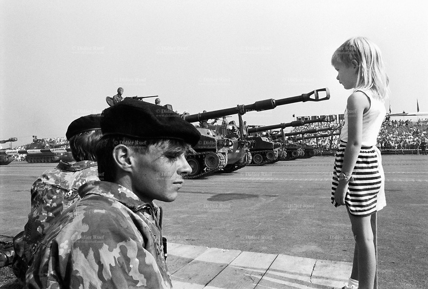 Switzerland. Canton Lucerne. Emmen. Military parade. Soldiers, tanks and a young girl. The tank's barrel is pointing at the child's face. © 1991 Didier Ruef