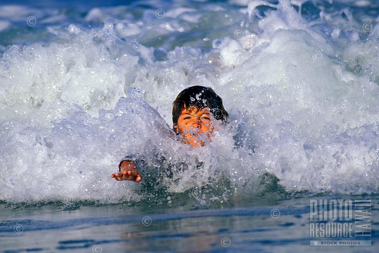 Boy body suring in wave on the Big Island