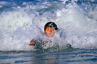 Boy body suring in wave on the Big Island