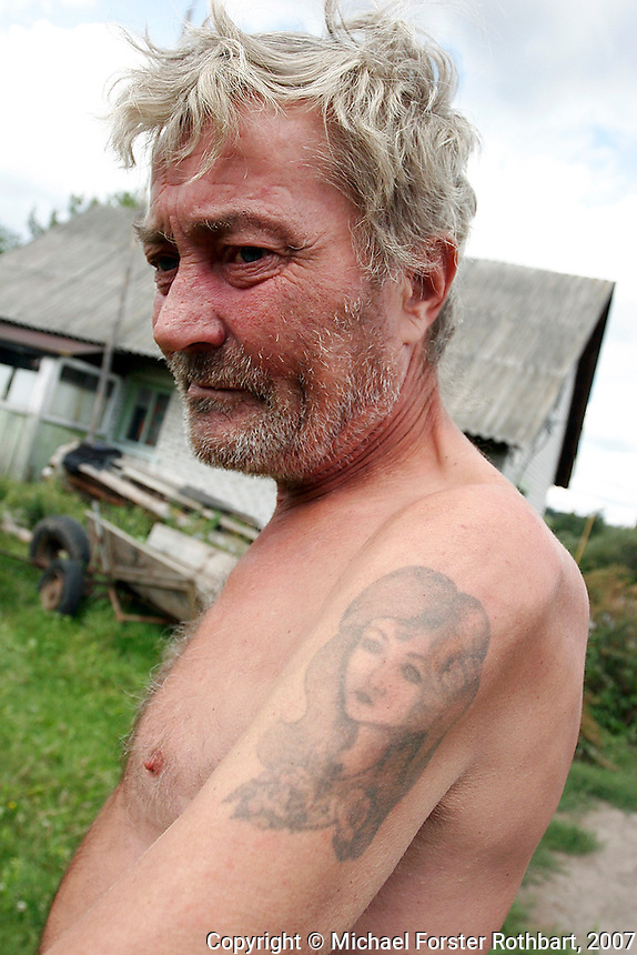"""""""I was born here and I'll die here. I already want to die. Forgive me, I'm drunk. I drink a lot now. We only have what God gives us, our health, our place, our friends."""" <br /> -- Vasily Oleksandrovich, farmer<br /> <br /> After his wife Natasha died in January 2007, Vasily tattooed her face on his shoulder as a personal memorial. She died from cancer after a long illness, a few days after her 46th birthday. He now lives alone, farming a small plot of land on the outskirts of Ivankiv, Ukraine, the closest inhabited city to the Chernobyl Exclusion Zone.   <br /> ------------------- <br /> This photograph is part of Michael Forster Rothbart's After Chernobyl documentary photography project.<br /> © Michael Forster Rothbart 2007-2010.<br /> www.afterchernobyl.com<br /> www.mfrphoto.com <br /> 607-267-4893 o 607-432-5984<br /> 5 Draper St, Oneonta, NY 13820<br /> 86 Three Mile Pond Rd, Vassalboro, ME 04989<br /> info@mfrphoto.com<br /> Photo by: Michael Forster Rothbart<br /> Date:  8/2007    File#:  Canon 20D digital camera frame 14285 <br /> ------------------- <br /> Original caption: .Photo title:.Vasily on his farm in Ivankiv..Caption:.After Vasily Oleksandrovich's wife Natasha died in January 2007, he had her face tattooed on his shoulder as a personal memorial. She died from cancer after a long illness, a few days after her 46th birthday. He now lives alone, farming a small plot of land on the outskirts of Ivankiv, the closest inhabited city to the Chernobyl Exclusion Zone...Quote: .""""I was born here and I'll die here. I already want to die. Forgive me, I'm drunk. I drink a lot now. We only have what God gives us, our health, our place, our friends."""" .-- Vasily Oleksandrovich, farmer.-------------------."""