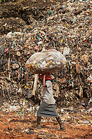 Nigeria. Enugu State. Enugu. Garbage collector on garbage heap. Scavenger at work. A lonely woman carries on her head a plastic blag full of plastic bottles and aluminium can which she will resell for money. The open air and uncontrolled rubbish dump shows the failure in the solid-waste management. Enugu is the capital of Enugu State, located in southeastern Nigeria.  2.07.19 © 2019 Didier Ruef