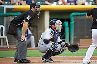 Humberto Quintero (35) of the Tacoma Rainiers behind the plate with home plate umpire Ryan Goodman as the Rainiers faced the Salt Lake Bees in Pacific Coast League action at Smith's Ballpark on July 8, 2014 in Salt Lake City, Utah.  (Stephen Smith/Four Seam Images)