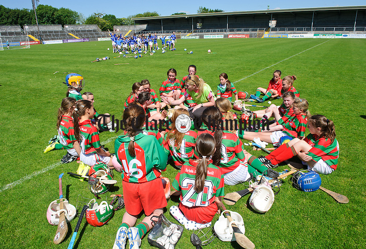 The defeated Quin team come to terms with their loss as victorious Kilmaley celebrate behind following the Div2B Primary Schools camogie final in Cusack park. Photograph by John Kelly.