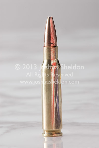 Bullets on marble surface with American flag reflected in barrel