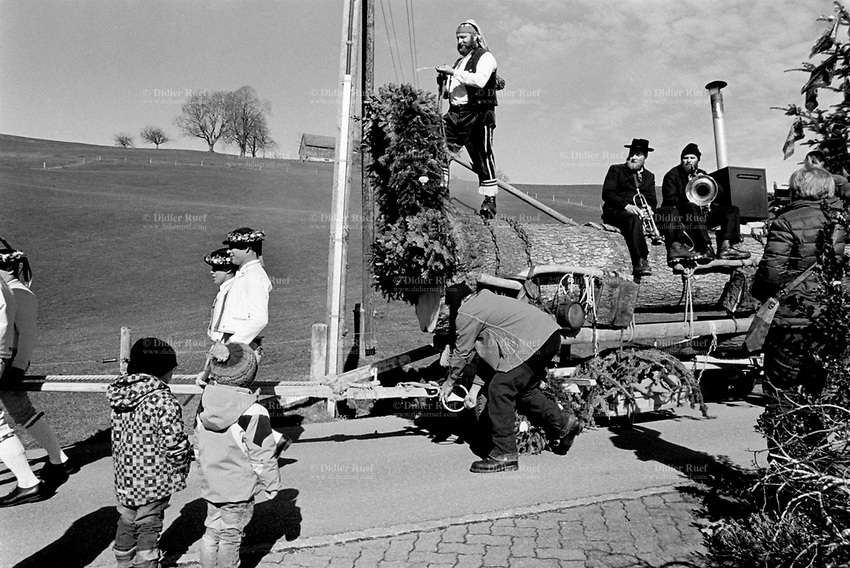 Switzerland. Canton Appenzell Ausserrhoden. Stein The Urnäsch Bloch Parade is a traditional historical procession where a group of men pull a chariot with a trunk from the last tree chopped in the winter. The men wear traditional Swiss garbs. Two small children watch the parade. The canton of Appenzell Ausserrhoden is also called in English Appenzell Outer Rhodes. 27.02.2017 © 2017 Didier Ruef