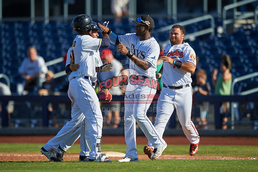 Peoria Javelinas Franchy Cordero (10), of the San Diego Padres organization, is congratulated by coach Yoel Monzon (back), Justin Williams (Rays), and D.J. Stewart (Orioles) after a walk off base hit during a game against the Scottsdale Scorpions on October 22, 2016 at Peoria Stadium in Peoria, Arizona.  Peoria defeated Scottsdale 3-2.  (Mike Janes/Four Seam Images)