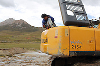 "A heavy-machinery operator takes a break. Construction in the region is increasing rapidly as the government implements its ""western development strategy,"" aimed at bringing prosperity to the region. The Tibetan Plateau is a fragile ecosystem and changes here will have far-reaching implications for all of Asia."