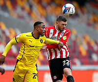 14th February 2021; Brentford Community Stadium, London, England; English Football League Championship Football, Brentford FC versus Barnsley; Henrik Dalsgaard of Brentford heads the ball away past Victor Adeboyejo of Barnsley