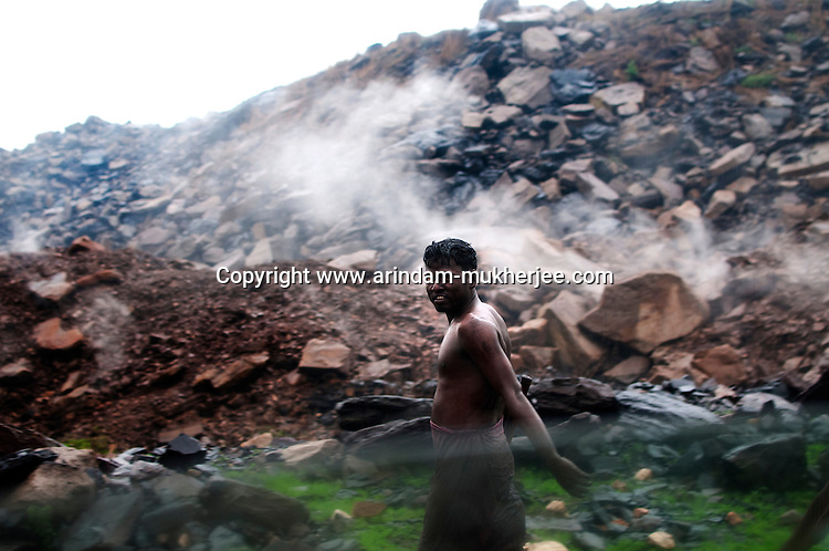 A miner returning home from work at Laltenganj, Jharia. Behind him poisonous gases and fumes from the fissures caused by burning coal seams underground create a curtain of smog . A huge coal mine fire is engulfing the city of Jharia from all its sides. All scientific efforts have gone in vain to stop this raging fire. This fire is affecting lives of people living in and around Jharia. Jharkhand, India. Arindam Mukherjee