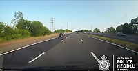 "Pictured: Dashcam video grab showing a blue Mini and a silver Ford Mondeo colliding in the distance on the M4 motorway near Port Talbot, Wales, UK in June 2018.<br /> Re: Two motorists have been convicted of dangerous driving following a road rage incident on the M4 near Port Talbot.<br /> Dash cam footage shows the two men repeatedly undertaking and tailgating each other along the eastbound carriageway in June last year.<br /> The incident eventually led to one of the vehicles – a blue Mini – flipping onto its roof with the driver fortunate to get out of the car unharmed.<br /> Paul Carpenter, aged 44, from Boxhill in Surrey, and Wayne Sebury, 59, from Pontypridd, initially denied any wrongdoing but later pleaded guilty to dangerous driving.<br /> They appeared at Cardiff Crown Court on Thursday 11th April where Carpenter was sentenced to six months in prison and disqualified from driving for 18 months. Sebury was given an 18 month community order and disqualified for 12 months. He must also carry out 150 hours unpaid work.<br /> PC Kathryn Matthews of the South Wales Police Roads Policing Unit said: ""This incident was a classic case of road rage where two motorists have driven dangerously, at high speeds, undertaking, tailgating and flashing their lights.<br /> ""It is sheer luck that nobody was killed or seriously injured and the dash cam footage of the incident sends out a clear message about the consequences of driving in such an irresponsible manner.""<br /> Expert witness evidence showed that Sebury drove his blue Mini and Carpenter his Ford Mondeo at speeds of upto 101mph shortly prior to the collision."