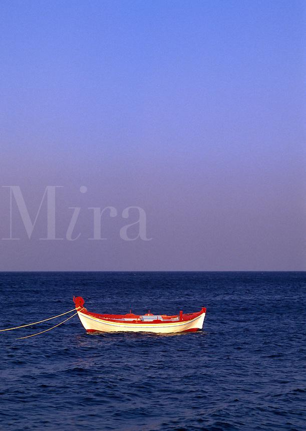 Fishing boat at anchor off beach at Kamari, Santorini, Greece.
