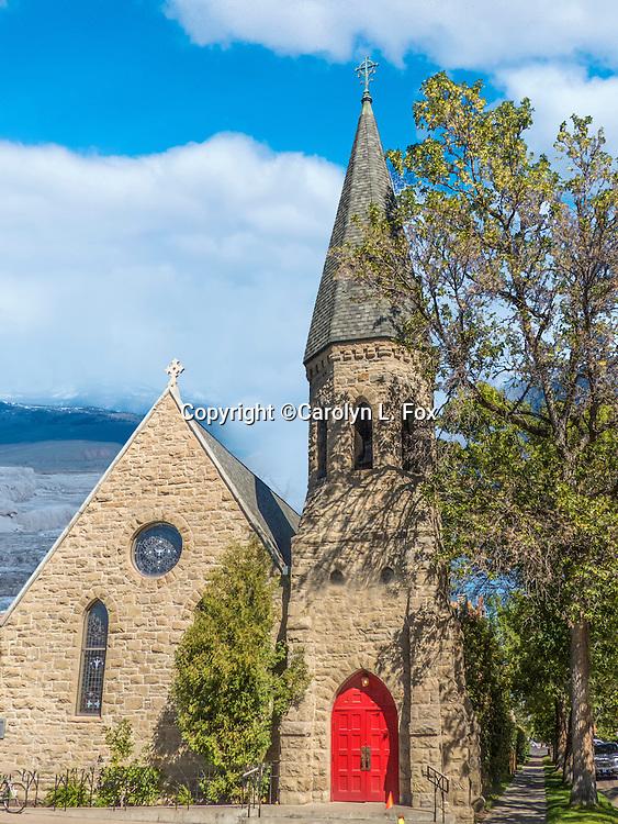 An old church sits by a sidewalk.