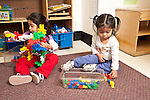 Education preschool 2-3 year olds two girls sitting near each other playing separately with either colored plastic sorting bears or colorful plastic connecting pieces