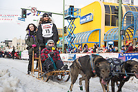Justin Savidis and team leave the ceremonial start line with an Iditarider at 4th Avenue and D street in downtown Anchorage, Alaska during the 2015 Iditarod race. Photo by Jim Kohl/IditarodPhotos.com