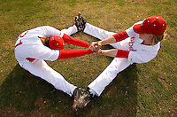 Two baseball players help each other stretch in the grass of the outfield.