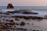 A long-exposure shot taken after sunset at Little Corona beach in Corona Del Mar (Newport Beach), CA, aiming at the distinctive arch rock off shore.  This was a two minute exposure, so the rocks were alternately covered and uncovered by water, giving them a ghostly feel, as though a low mist was over the ground.