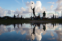 People play volleyball next to a flooded area near the airport runway, in downtown Funafuti. Parts of the island flood at this time of the year due to the 'king tides'. The king tides are seasonal and are characterised by very high water levels in the surrounding ocean. At this time of year the waves inundate the coastline but also water seeps up through the ground which is made of porous coral. This natural phenomenon is particularly serious for Tuvalu, a low-lying atoll island nation, whose highest point is only a few metres above sea level. As sea levels rise, the king tides regularly flood parts of the island and will likely increase in severity in the future, potentially making large parts of the nation uninhabitable. Funafuti, Tuvalu. March, 2019.