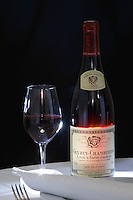 A bottle of Maison Louis Jadot Gevrey Chambertin Lavaux Saint St Jacques 2002 red burgundy wine and a glass of red wine standing on a table top with a white cloth a fork and a napkin. Backlit backlight back light lit Black background, Maison Louis Jadot, Beaune Côte Cote d Or Bourgogne Burgundy Burgundian France French Europe European
