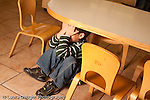 Preschool Headstart 3-5 year olds sad isolated boy sitting under child-size table in classroom at school covering face with hands horizontal