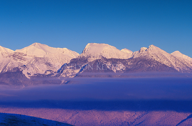 A layer of fog over the Mission valley casts a shadow on the snow covered peaks of the Mission Mountains at sunset
